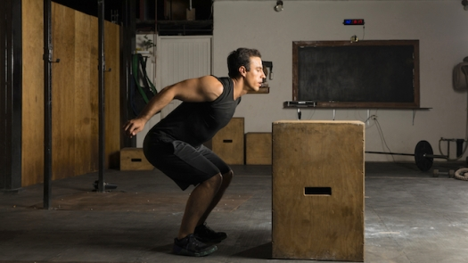 Young man jumping a box at the gym
