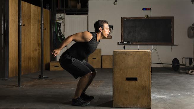 Young man jumping a box at the gym