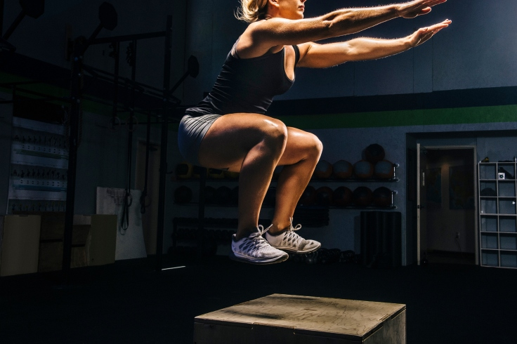 Young woman jumping mid air on gym box with arms reaching out